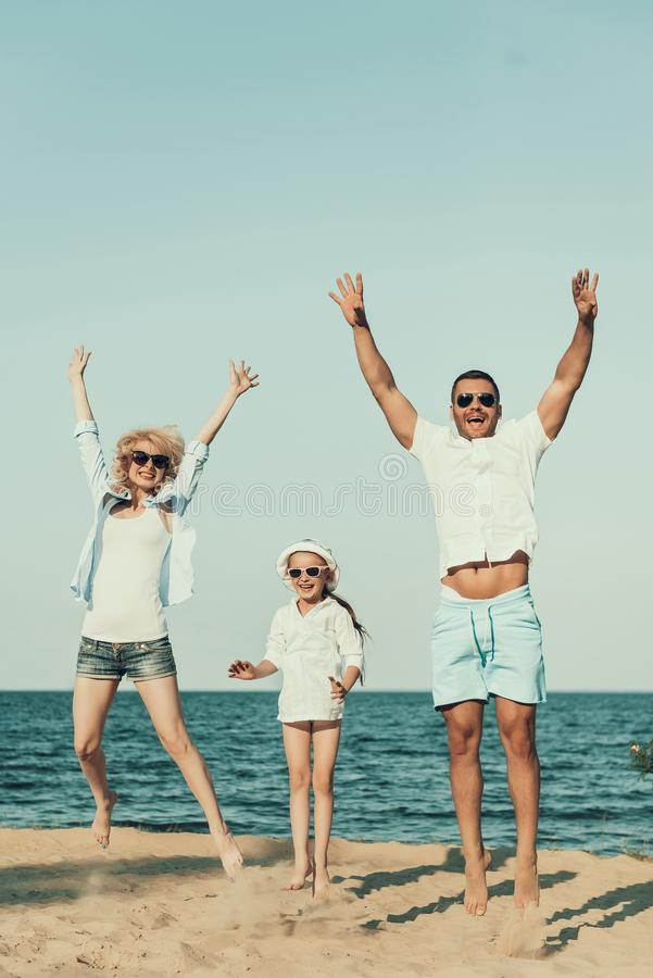 Young family sports on beach, jumping on sand. royalty free stock photo