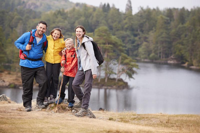 Young family standing on a rock by a lake looking to camera embracing, full length stock photography