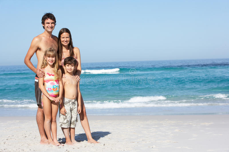 Young Family Standing On Sandy Beach on Holiday royalty free stock image