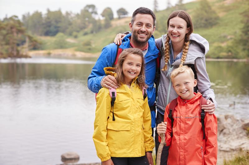 Young family standing on the shore of a lake in the countryside looking to camera smiling, Lake District, UK stock photos