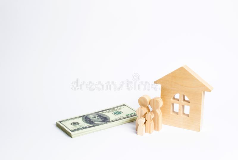 A young family stands near a wooden house and with a bundle of money. The concept of a strong family, the continuation. Of the family. Loans for the purchase of royalty free stock image