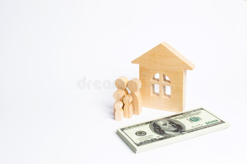 A young family stands near a wooden house and with a bundle of money. The concept of a strong family. The continuation of the family. Loans for the purchase of royalty free stock photos