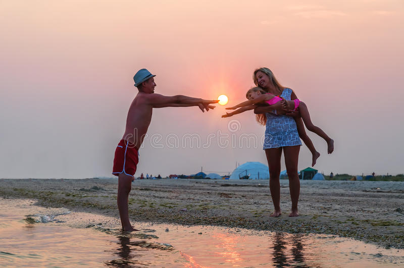 Young family, sunset royalty free stock image