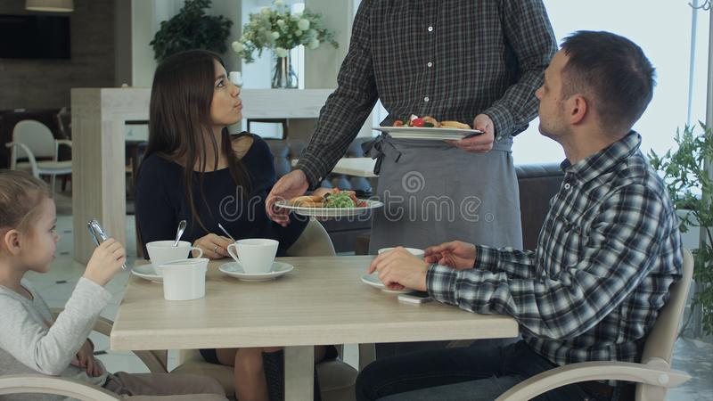 Young family take a meal in cafe or restaurant. Waiter make a mistake and confuse dishes. Father and mother looking stock image