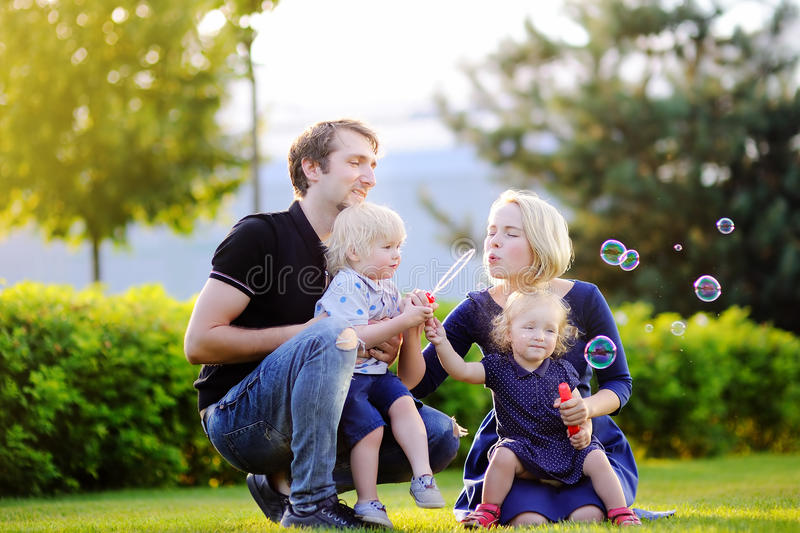 Young family with their toddler children blowing soap bubbles. Outdoors on sunny summer day royalty free stock images