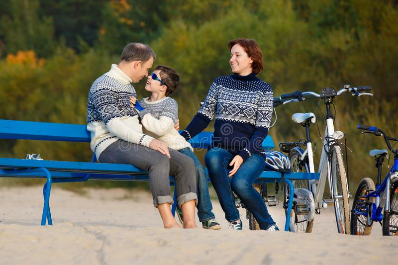 Young family of three having rest on bench during their bike riding on beach stock photo