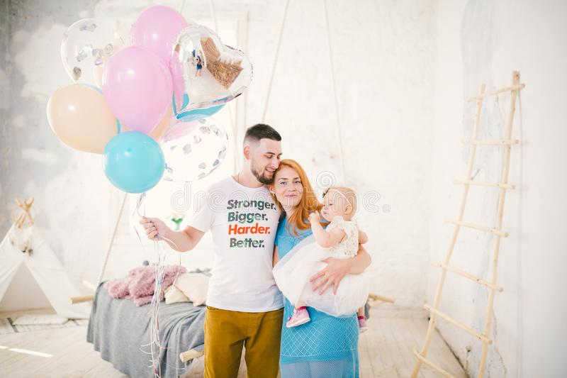 A young family of three people, mom`s dad and daughter`s one year old stands inside the room. Holding a balloon in her hand, a w. A young family of three people royalty free stock photos