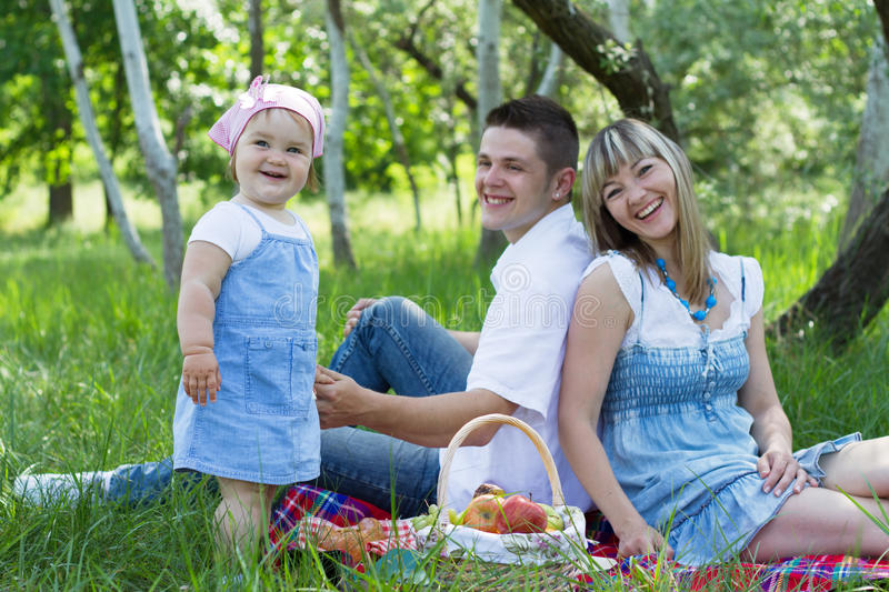 Young family of three on a picnic. Young beautiful family of three on a picnic royalty free stock photo