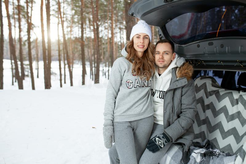A young family of travelers guy and girl are sitting in the trunk of his car in an embrace. A walk of a young couple in the winter. Pine forest. Winter active royalty free stock photography