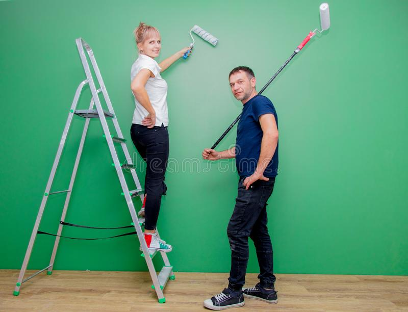 Young family is trying to paint a wall in their room royalty free stock photography