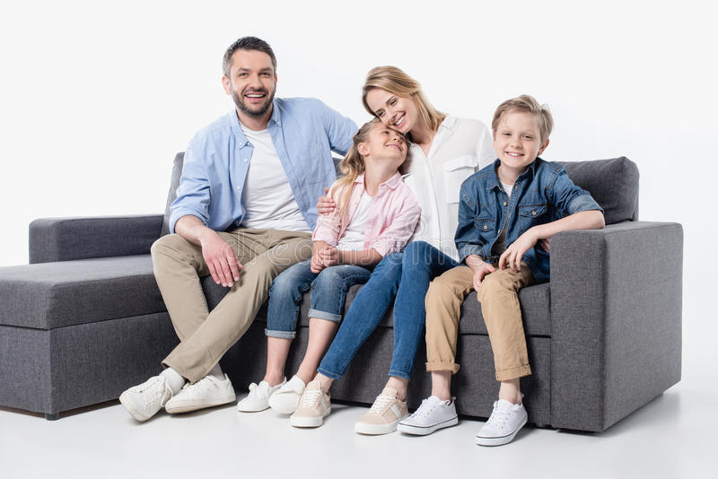Young family with two children sitting together on couch isolated on white. Happy young family with two children sitting together on couch isolated on white stock photography