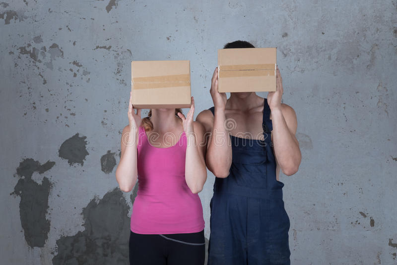 Young family of two loving people parses boxes in the new apartment on the background of a dirty wall stock photos