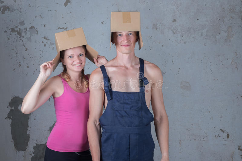 Young family of two loving people parses boxes in the new apartment on the background of a dirty wall royalty free stock photography