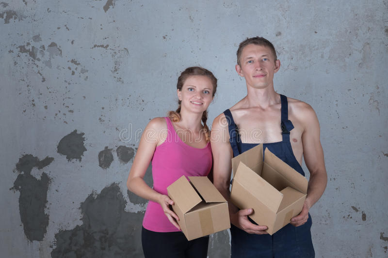 Young family of two loving people parses boxes in the new apartment on the background of a dirty wall royalty free stock image