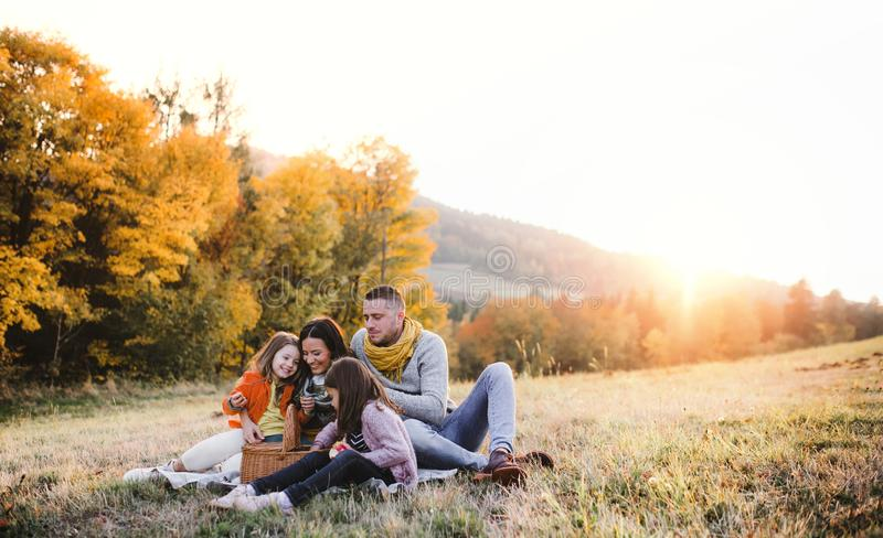 A young family with two small children having picnic in autumn nature at sunset. A portrait of happy young family with two small children sitting on a ground in stock photography