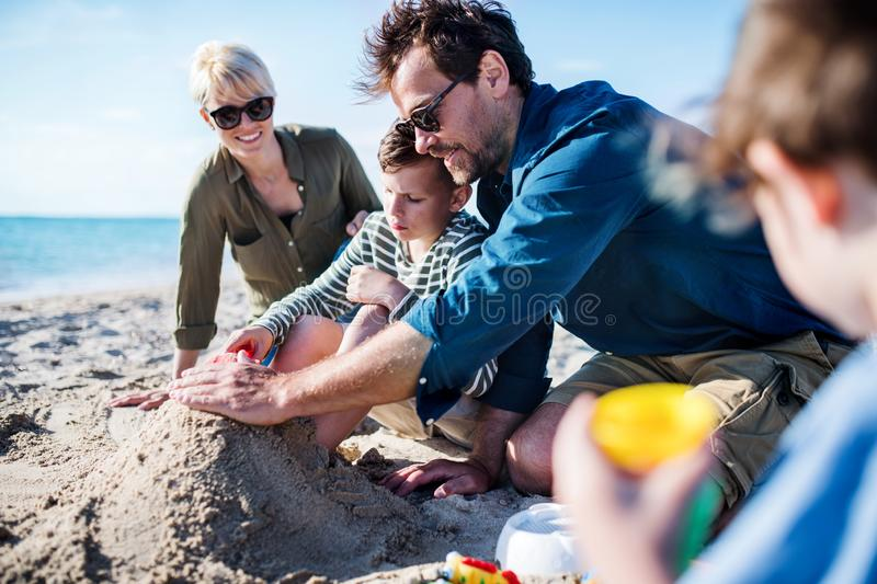 Young family with two small children sitting outdoors on beach, playing. royalty free stock image