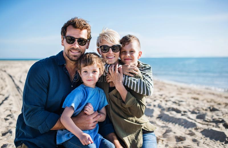 Young family with two small children sitting outdoors on beach. royalty free stock image