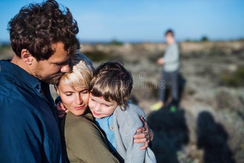 Young family with two small children standing outdoors in nature. stock photography