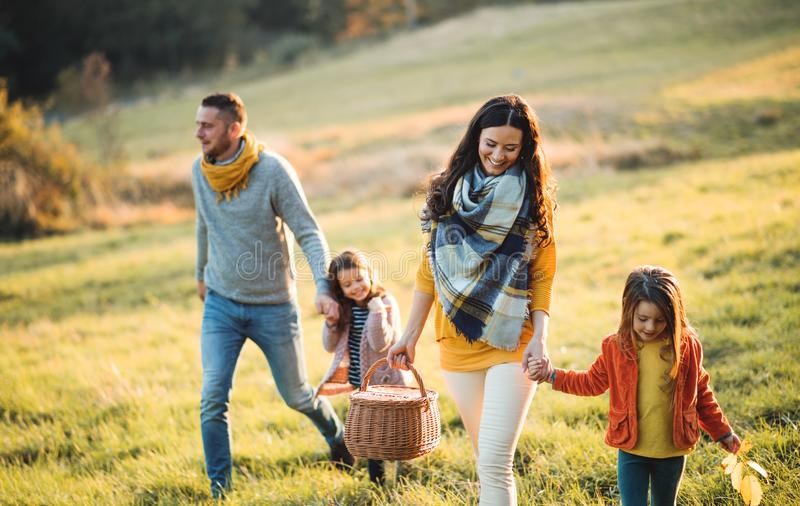 A young family with two small children walking in autumn nature. royalty free stock photos