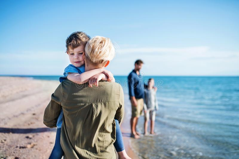 Young family with two small children walking outdoors on beach. stock photo