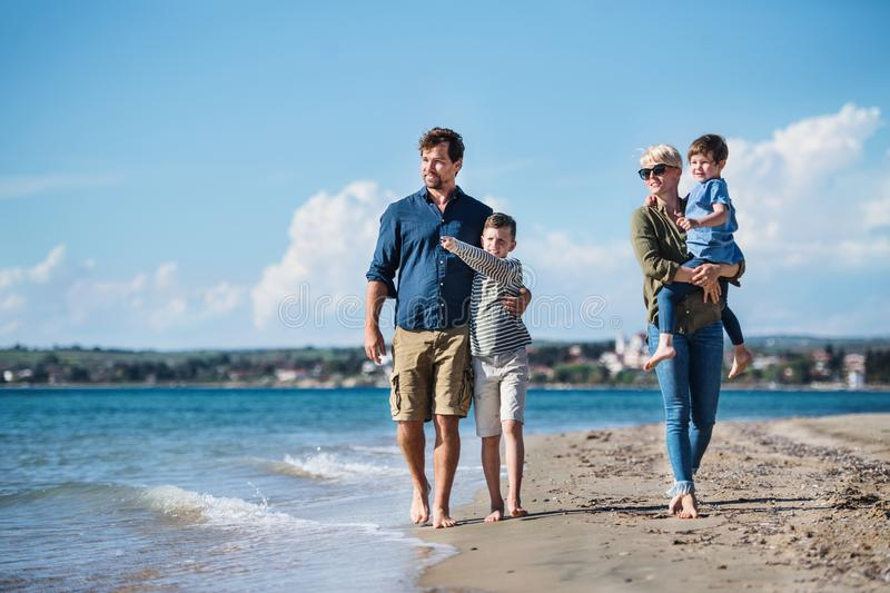 Young family with two small children walking outdoors on beach. royalty free stock image