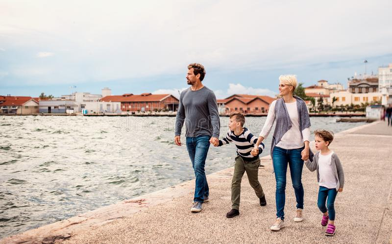 Young family with two small children walking outdoors on beach, holding hands. royalty free stock photo