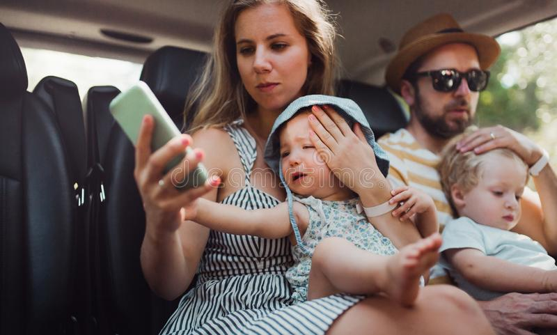 A young family with two toddler children in taxi on summer holiday. stock images