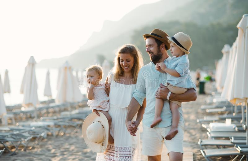 A young family with two toddler children walking on beach on summer holiday. stock photo