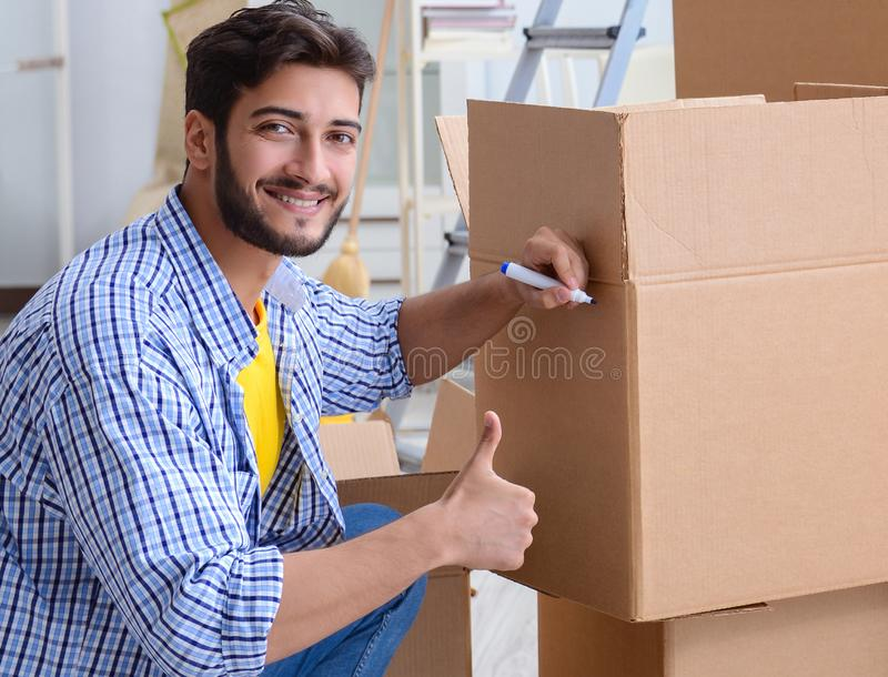 Young family unpacking at new house with boxes royalty free stock images