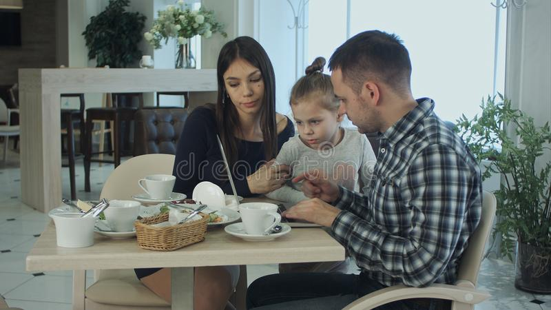 Young family using laptop, chatting and smiling in cafe or restaurant. stock images