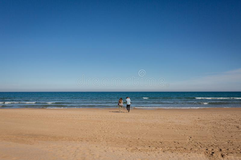 Young family walking in empty beach Gandia, Spain. Young family walking in empty nice beach Gandia, Spain royalty free stock image