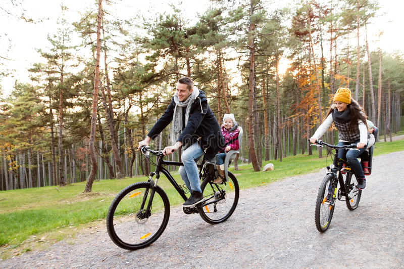 Young family in warm clothes cycling in autumn park. Beautiful young family with two daughters in bicycle seats in warm clothes cycling outside in autumn nature royalty free stock photos