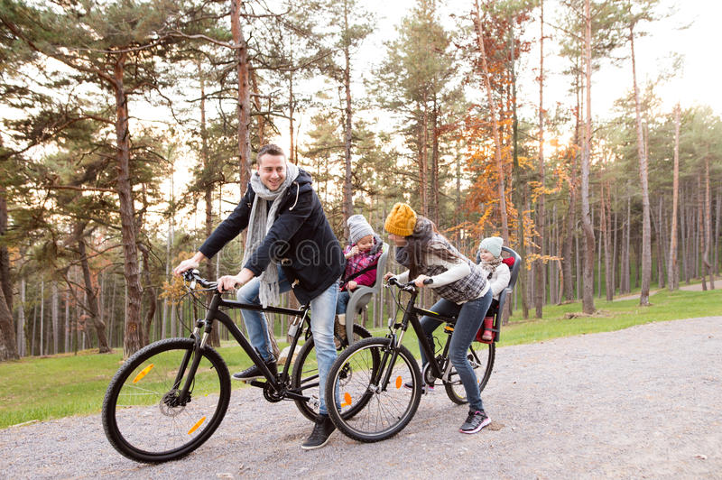 Young family in warm clothes cycling in autumn park. Beautiful young family with two daughters in bicycle seats in warm clothes cycling outside in autumn nature stock photos