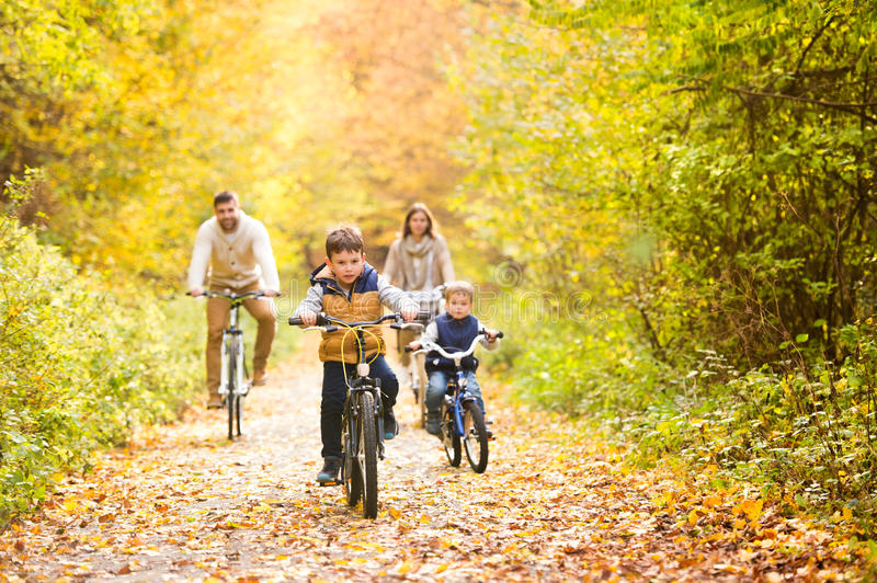 Young family in warm clothes cycling in autumn park. Beautiful young family with two sons in warm clothes cycling outside in autumn nature stock photo