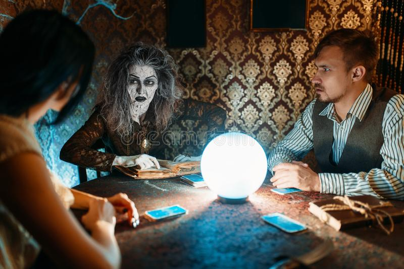 Family and witch at the table with crystal ball. Young family and witch at the table with crystal ball on spiritual seance, scary wizard reads the spell. Female stock photos