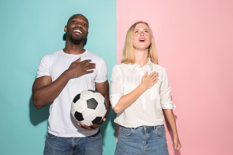 The young fans singing national anthem on blue and pink trendy colors. The young fans singing national anthem on blue and pink trendy color studio background stock photo