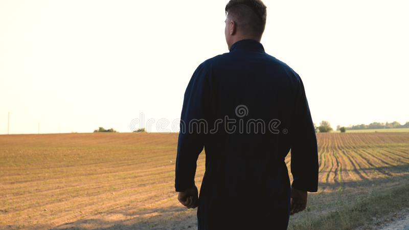 A young farmer in a blue robe walks the field looking at planted plants. Concept: clean air, bio, agriculture. royalty free stock images