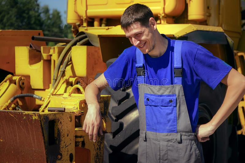 Young farmer smiles on the background of the tractor stock image