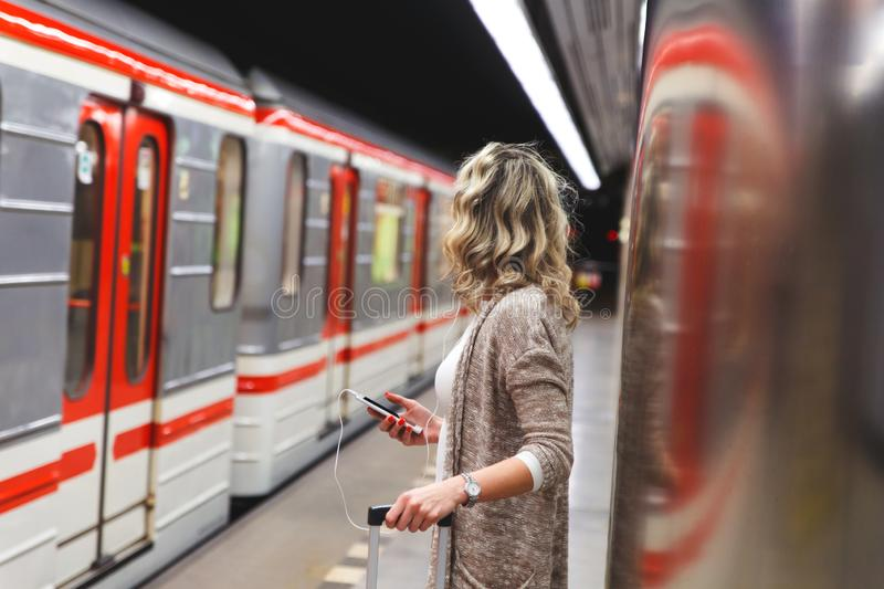 Young farmer standing in field.Young woman with suitcase waiting train in metro station. royalty free stock photo