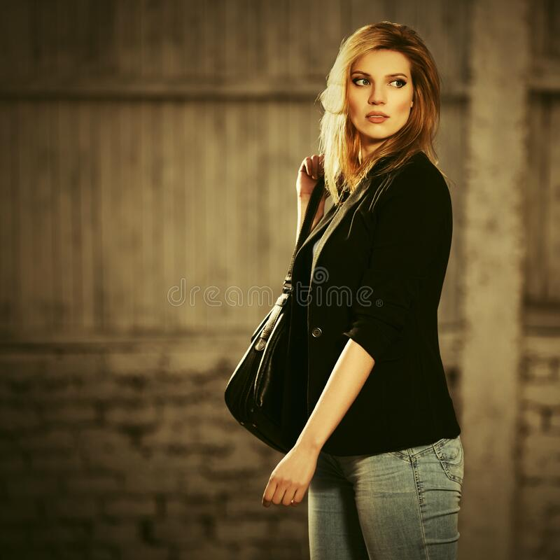 Young fashion blond business woman with handbag walking on city street stock photos