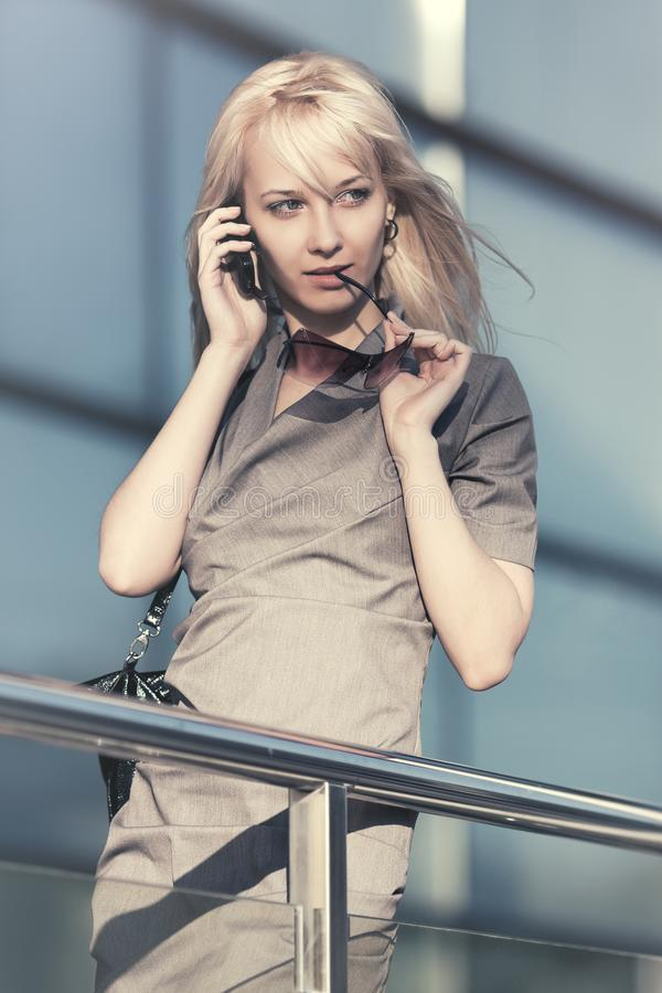Young fashion business woman talking on mobile phone next to office royalty free stock image
