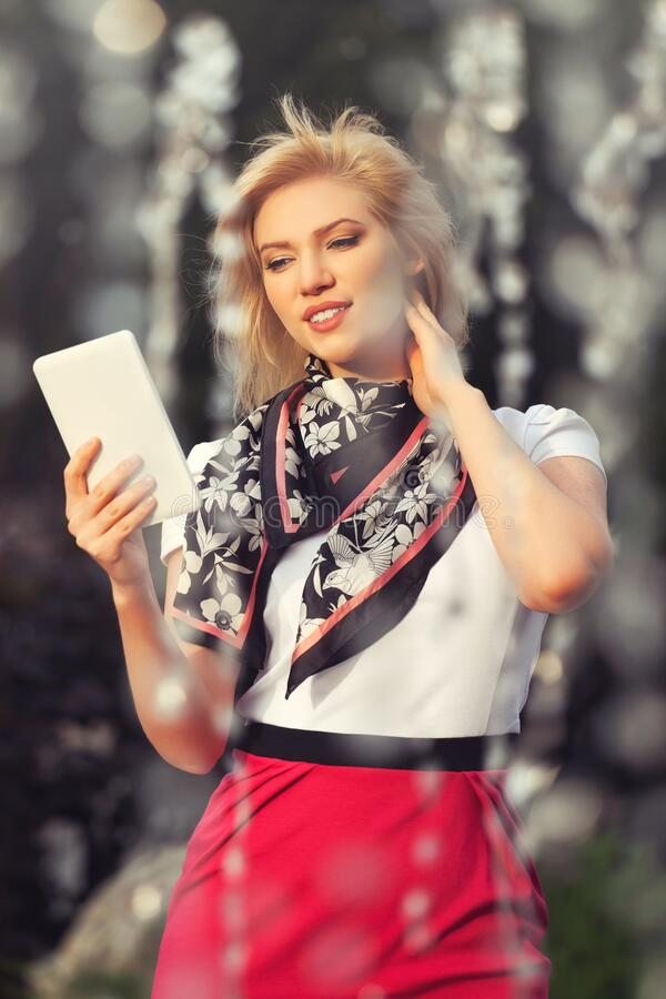 Young fashion blond business woman using tablet computer walking on city street stock photo