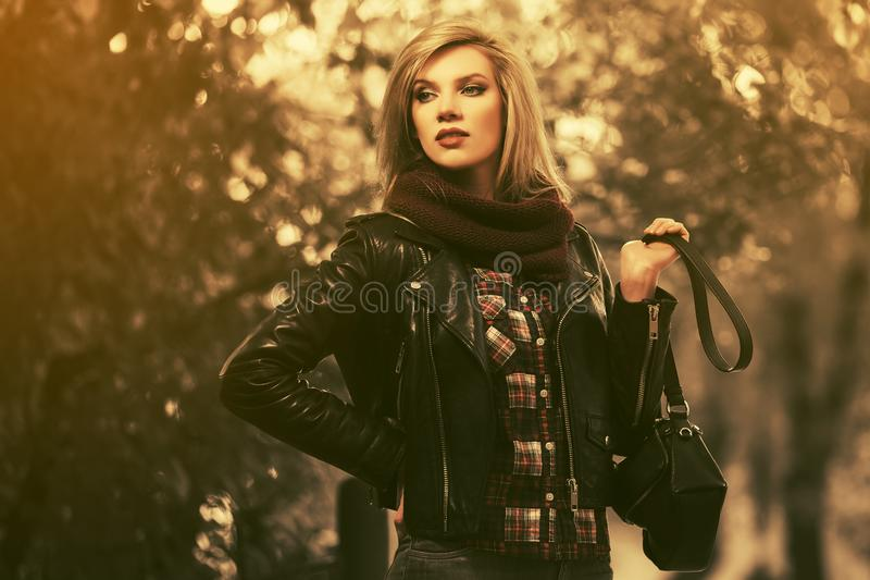 Young fashion blond woman in black leather jacket walking in city park royalty free stock photography