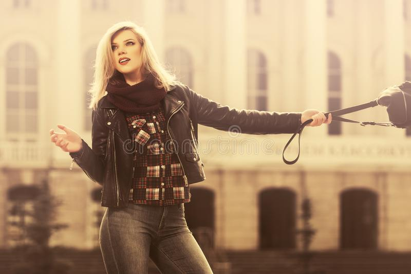 Young fashion blond woman in black leather jacket walking on city street stock photos