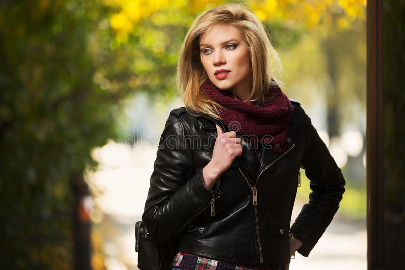 Young fashion blond woman in leather jacket in autumn park royalty free stock photography