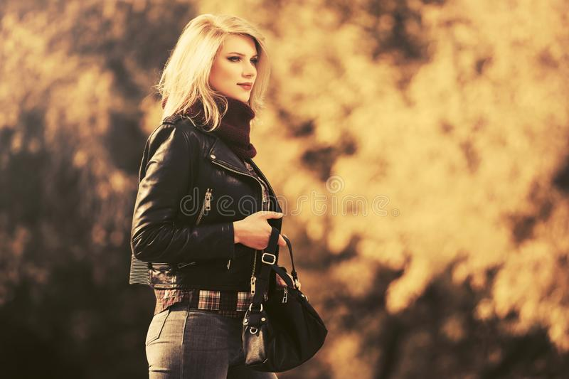 Young fashion blond woman in leather jacket walking outdoor royalty free stock photography