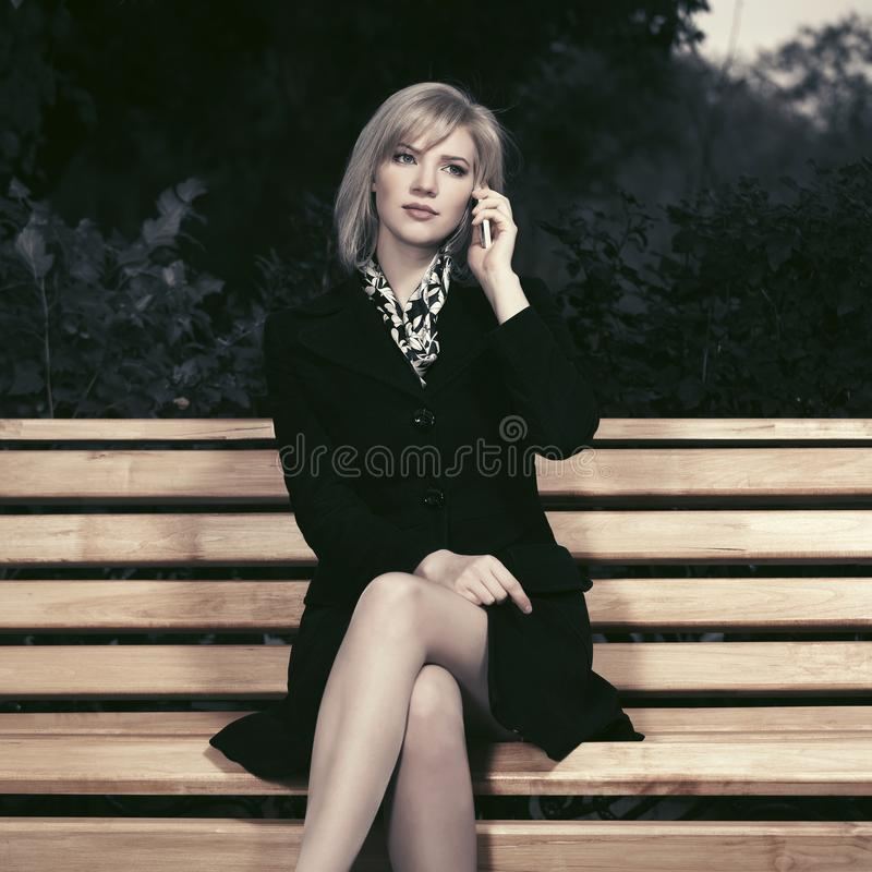 Young fashion blond woman talking on mobile phone sitting on bench royalty free stock images