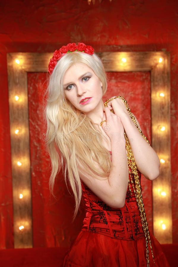 Young fashion blonde lady posing in red corset dress on red fashion background with lamp bulbs frame with yellow warm royalty free stock photo