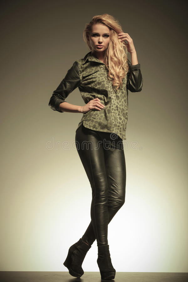 Young fashion blonde woman in leather pants posing royalty free stock images