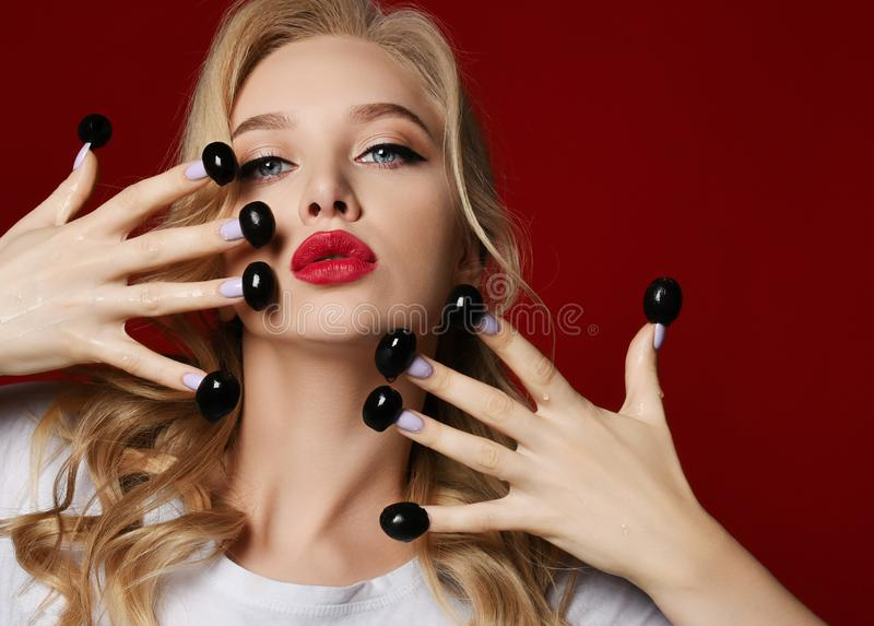 Young fashion blonde woman with red lips eat black olives from finger nails. On red background royalty free stock photography